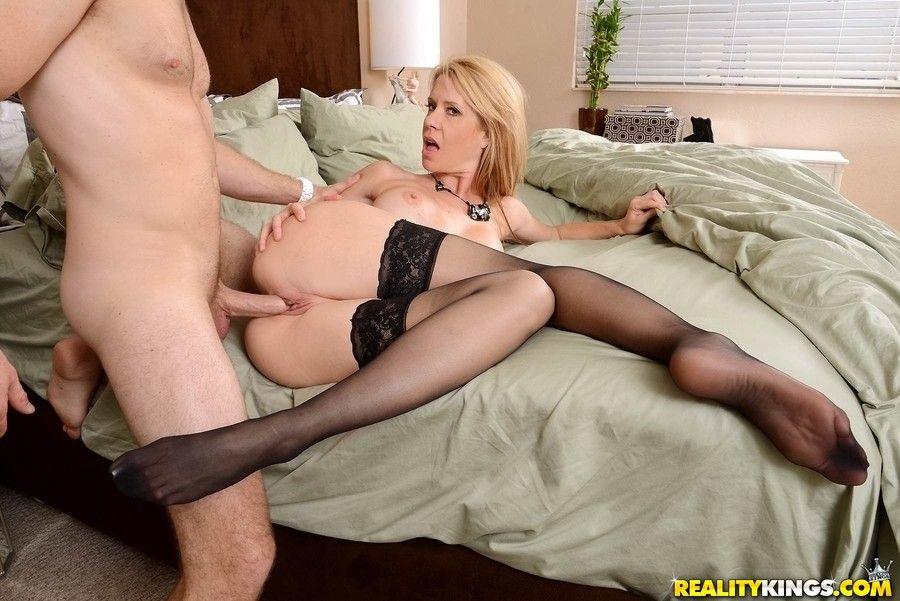 Порно парень трахает зрелую блондинку в чулках а кровати